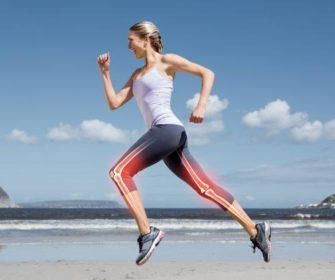 A fit, young woman running on the beach.