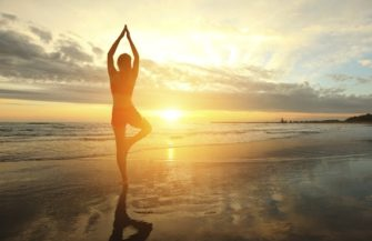 Young woman silhouette practicing yoga on the beach at sunset.